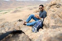 吃快餐的远足者在一座山边缘在沙漠 免版税库存照片