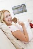 吃怀孕的电视注意的妇女的choc 免版税库存图片