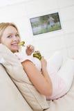 吃怀孕的电视注意的妇女 免版税库存图片