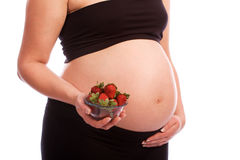 吃怀孕的草莓妇女的白种人 免版税库存照片