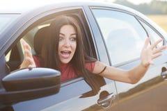 吃惊的美丽的女性惊叹与震动,姿态用手,神色通过车窗,注意事可怕在路 免版税图库摄影