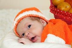 吃惊的逗人喜爱的新出生的婴孩在一套被编织的橙色服装穿戴了 免版税库存照片