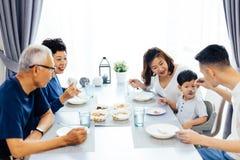 吃愉快的亚洲的大家庭晚餐在家充分笑声和幸福 免版税图库摄影
