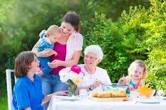 吃愉快的祖母与她的家庭的午餐 免版税库存图片
