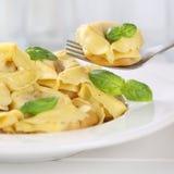 吃意大利式饺子面团与蓬蒿的意大利烹调面条膳食 图库摄影