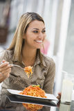 吃意大利面食妇女的咖啡馆 库存图片