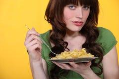 吃意大利面食的妇女 免版税库存图片
