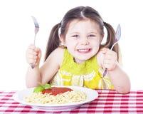 吃意大利面食的美丽的女孩 免版税库存图片