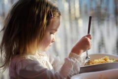 吃意大利面食的逗人喜爱的小女孩 库存照片