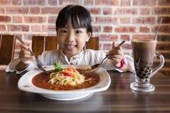 吃意粉博洛涅塞的亚裔中国小女孩 库存图片