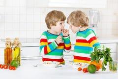 吃意粉的两个小孩男孩在国内厨房里 库存图片