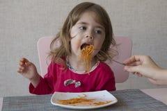吃意粉的可爱的小女孩画象坐在桌上 免版税库存图片