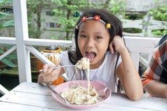 吃意粉的女孩。 库存照片