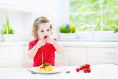 吃意粉的逗人喜爱的小孩女孩在一个白色厨房里 免版税库存图片