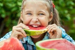 吃成熟西瓜的女孩 免版税图库摄影