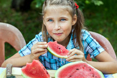 吃成熟西瓜的女孩 免版税库存图片