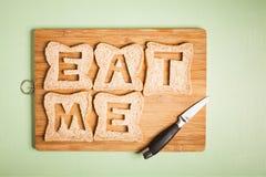 吃我文本被雕刻在黑面包切片外面 免版税库存图片