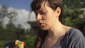 吃户外热狗用番茄酱的年轻可爱的妇女 影视素材
