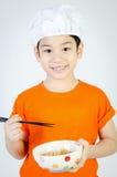 吃拉面面条的亚裔逗人喜爱的孩子 免版税库存图片