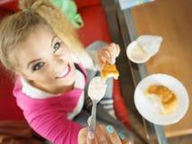 吃新月形面包和酸奶的妇女 库存照片
