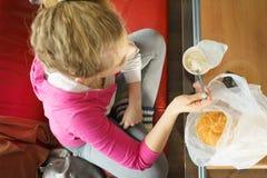 吃新月形面包和酸奶的妇女 免版税图库摄影