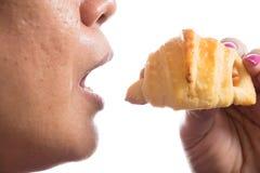 吃新月形面包用热狗的妇女隔绝在白色背景 免版税库存图片