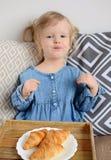 吃新月形面包的1,11年的小的女婴年龄 库存照片