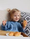 吃新月形面包的1,11年的小的女婴年龄 免版税库存图片