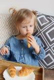 吃新月形面包的1,11年的小的女婴年龄 图库摄影