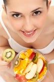 吃新鲜水果女孩沙拉 免版税图库摄影