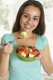 吃新鲜水果少年女孩的沙拉 免版税库存照片