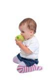 吃新鲜的女孩绿色年轻人的苹果婴孩 库存图片