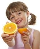 吃新鲜的桔子的愉快的小女孩 库存图片