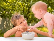 吃新鲜的水多的莓果的Sibings 愉快童年的概念 健康的食物 孩子医疗保健  小孩吃 库存图片