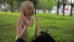 吃新鲜的沙拉在公园,健康素食食物的健身妇女 股票录像