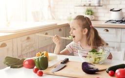 吃新鲜的沙拉的小女孩 免版税库存图片