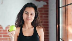 吃新鲜的绿色苹果的西班牙微笑的健身少女画象看照相机 股票录像