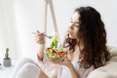 吃新鲜的绿色饮食沙拉的年轻少年穿戴睡衣 图库摄影
