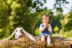 吃新鲜的苹果的小女婴在夏天公园。 免版税库存照片