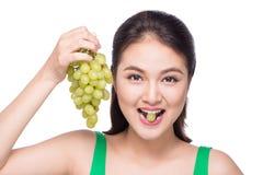 吃新鲜的葡萄的年轻美丽的亚裔妇女隔绝在丝毫 免版税库存图片