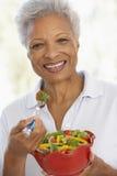 吃新鲜的蔬菜沙拉前辈妇女 免版税库存图片