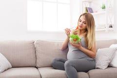 吃新鲜的蔬菜沙拉的年轻人孕妇 免版税库存照片