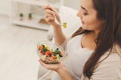 吃新鲜的蔬菜沙拉的年轻人孕妇 库存图片