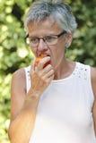 吃新鲜的蕃茄的成熟妇女。户外 免版税库存照片