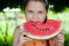 吃新鲜的西瓜的女孩 免版税库存图片