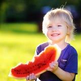 吃新鲜的西瓜的小男孩户外 免版税图库摄影