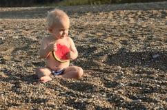 吃新鲜的西瓜的逗人喜爱的男婴在海滩 免版税库存图片