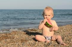 吃新鲜的西瓜的逗人喜爱的男婴在海滩 免版税库存照片