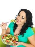 吃新鲜的酥脆混杂的庭院沙拉的健康少妇 免版税库存图片