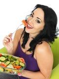 吃新鲜的酥脆混杂的庭院沙拉的少妇 免版税库存照片
